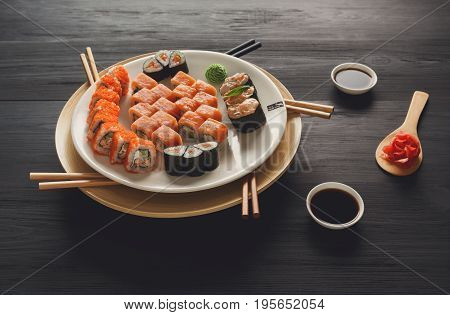 Japanese food restaurant, california salmon rolls, gunkans and sushi platter. Set with chopsticks and soy sauce. POV view on black background