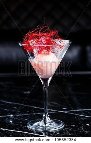 one scoop of the Strawberry ice cream in martini glass on the black marble background