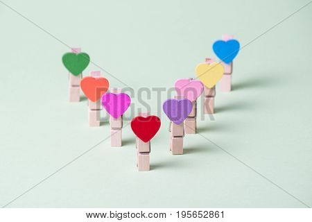 Colored heart shaped clothespins in row on greenery background