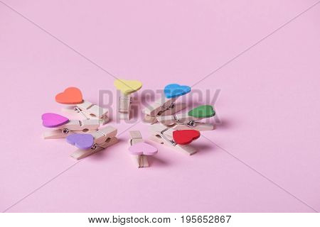 Colored heart shaped clothespins compose circle on pink background