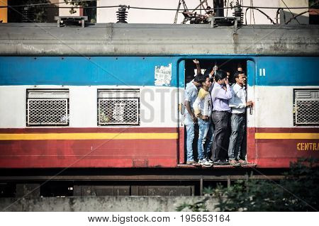 MUMBAI, INDIA - November 10 2017: Commuters on a crowded train hang at the door of an old train in Mumbai, India