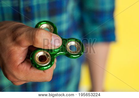 Male hand holding popular fidget spinner toy - close up.