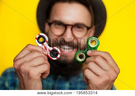 Happy young man holding two fidget spinners, focus on foreground. Trendy toy 2017