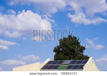 Solar powered house with solar panels on the roof with a tree behind it against blue sky and clouds