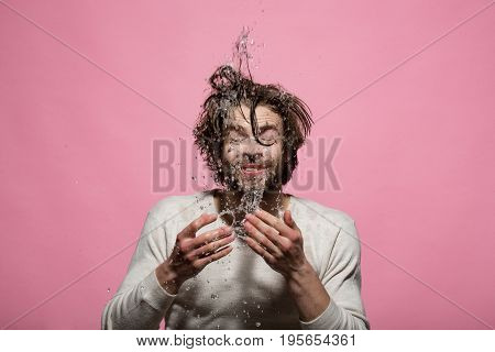 morning hygiene of man washing face with water drops. guy with long hair refreshing in underwear on pink background skincare health and wakeup everyday life barbershop