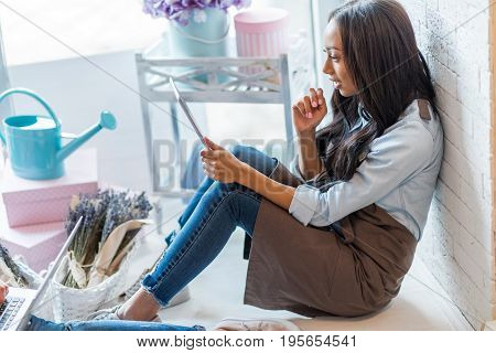 Side View Of Young African American Woman In Apron Using Digital Tablet While Sitting In Flower Shop