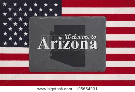 Welcome to Arizona with state map on a black chalkboard on a United States of America flag