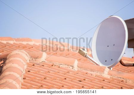 White satellite dish installed on rooftop with blue sky