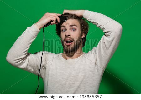 surprised man shaving with electric razor or shaver trimmer with long hair and beard on face in white underwear on green background morning and everyday life barbershop and fashion