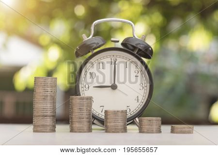 pile coin with clock on green bokeh light background. time is money and goal concept.