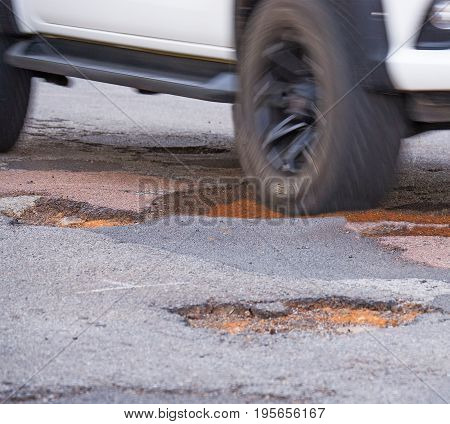 Car with big wheels and tires driving into a big pothole