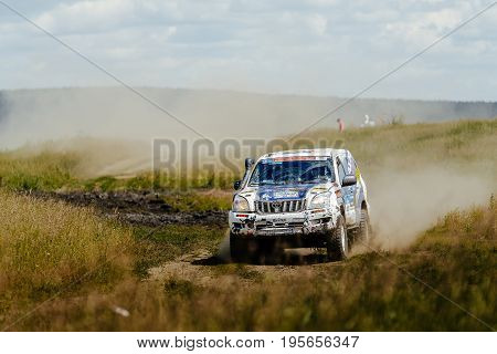 Filimonovo Russia - July 10 2017: rally car Toyota driving on a dust road among grass during Silk way rally