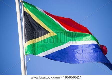 Raised South-African flag on a flag pole waving in the wind against blue sky