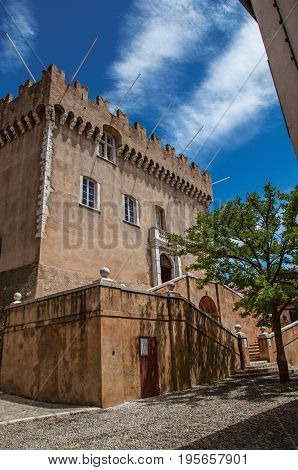 View of alley with trees and facade of the Grimaldi Castle in Haut-de-Cagnes, a pleasant village on top of a hill, near Nice. In the Alpes-Maritimes department, Provence region, southeastern France