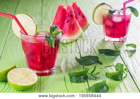 Watermelon cocktail in two glasses with slices of watermelon lime mint and ice melon mojito. Homemade lemonade with watermelon and red striped straw on green wooden table. Summer drink.