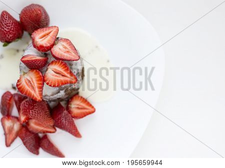 Delicious homemade chocolate cake with fresh red strawberries and cream sauce on white plate