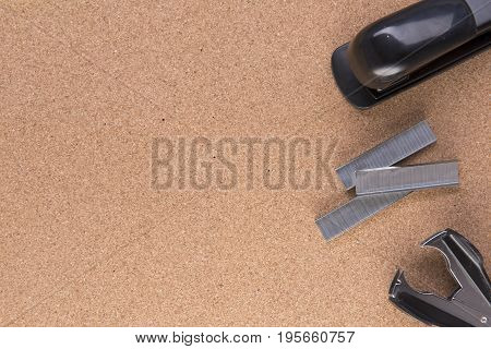 Background image with staples and a stapler on a cork board with copy space
