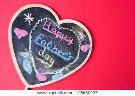 Happy father's day written by a child with colorful chalk on a heart shaped chalk board on red background