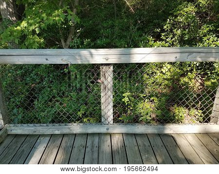 wood fence with metal wire and boardwalk and plants