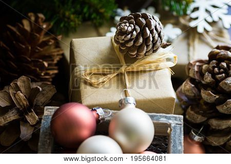Gift boxes for Christmas and New Year wrapped in craft paper pine cones fir tree branches colorful baubles rustic style authentic kinfolk hygge cozy