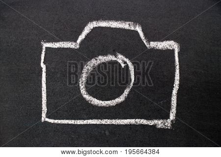 White chalk hand drawing as camera icon on black board background