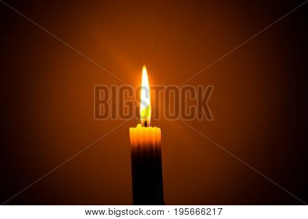 Close-up of a single litted candle light in the dark