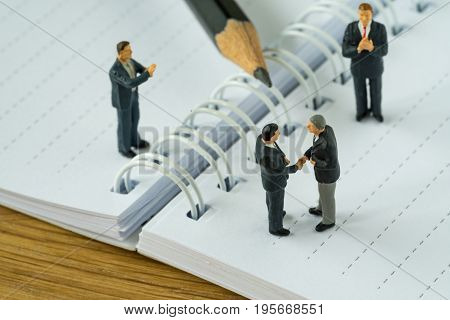 Miniature people with businessmen handshaking and others clapping on white note and pencil as business agreement concept.