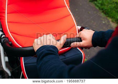 hands of men carry the stroller wet asphalt