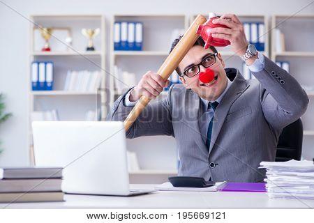 Clown businessman with a baseball bat and a piggy bank