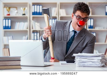 Clown businessman  in the office with an axe