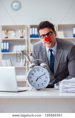 Clown businessman in the office with an axe and an alarm clock