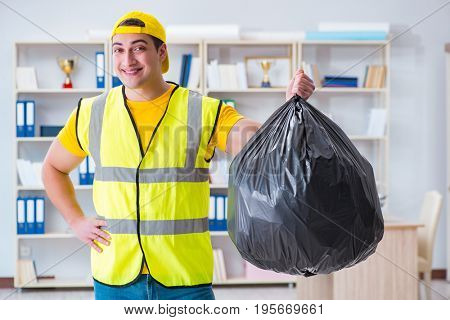 Man cleaning the office and holding garbage bag