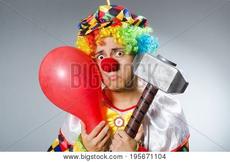 Clown with a hammer grey background isolated