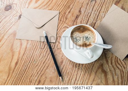 Coffee cup pencil and envelope on wood table background.