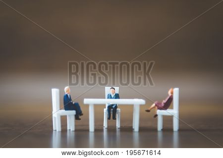 Miniature People Team Sitting Down On The Chair