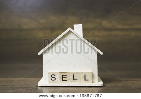 House model with Sell word on wooden blocks. Home finance concept