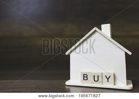 House model with buy word on wooden blocks. Home finance concept