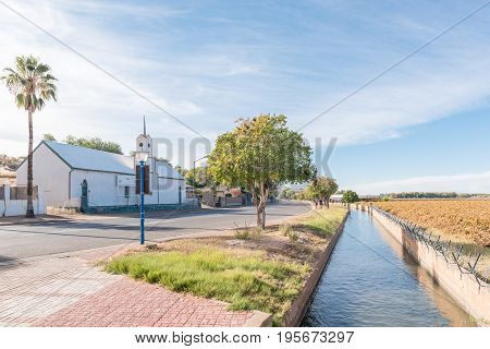 KEIMOES SOUTH AFRICA - JUNE 12 2017: The historic Dutch Reformed Mission Church in Keimoes now a museum an irrigation canal and vineyard next to the main road in Keimoes in the Northern Cape