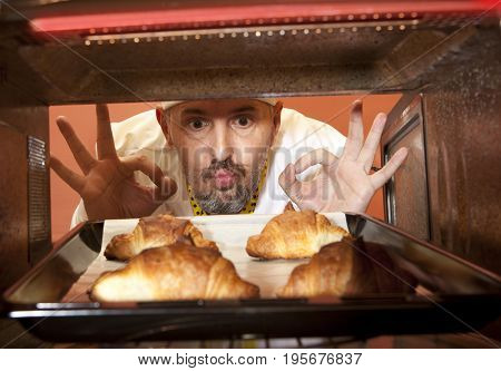 Chef prepares croissant in the oven. View from the inside of the oven