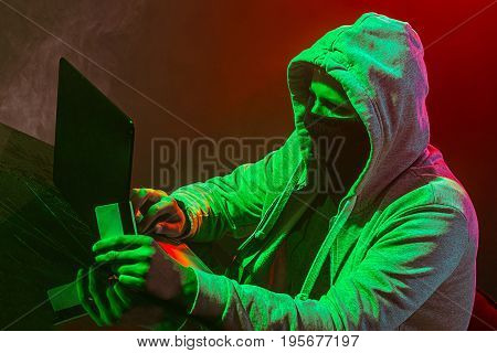 Hooded computer hacker stealing information with laptop on colored studio background