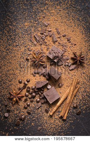 Food dessert background. Pieces of dark chocolate powder drops and spices.