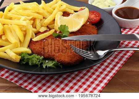 Dish Of Wiener Schnitzel And French Fries Served With Sauces And Salad On Rustic Wooden Table