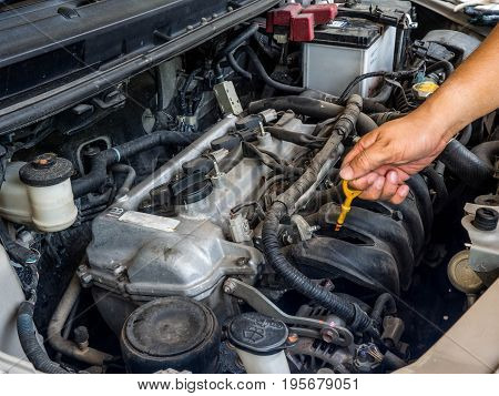 Hand of car mechanic working in auto repair service. He have fix old car engine streaked with dust and oil stains