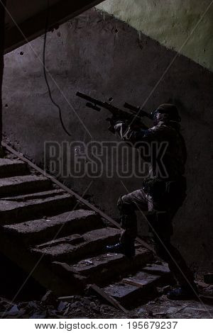 Military man with gun on stairs at entrance of ruined house