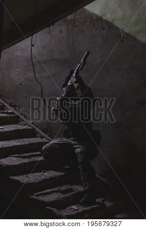 Strikeball player with weapons on stairs in entrance of destroyed house