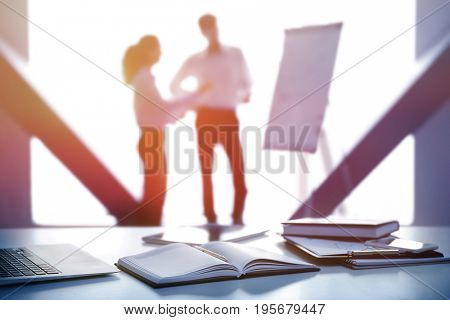 Workplace with notebook and people on background. Consulting service concept