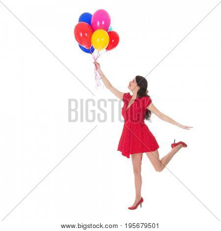 Young woman with red dress flying with a bunch of balloons