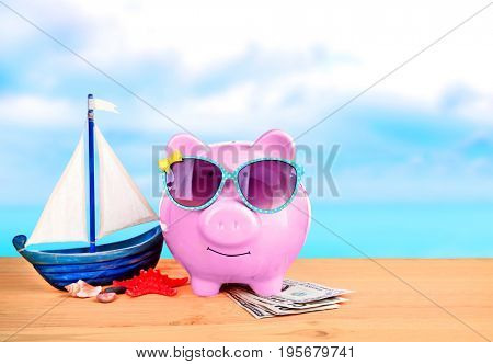 Piggy bank with sunglasses and money on wooden table against seascape background. Concept of money for vacation