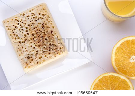 Crumpet on a white plate with orange juice and an orange cut in half