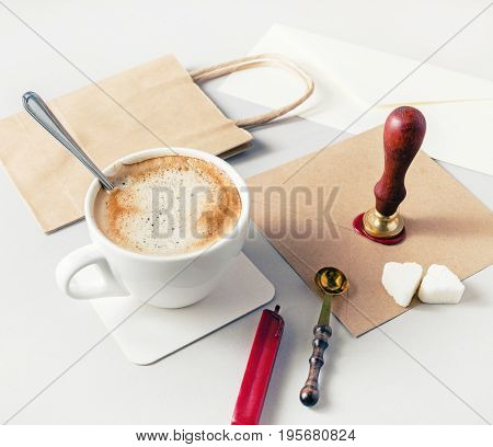 Still life with stationery and coffee cup on paper background. For design presentations and portfolios. Corporate identity template.